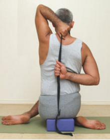 A person sitting in modified Gomukhasana.