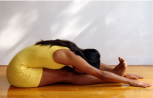 A yoga student in a seated forward bend.